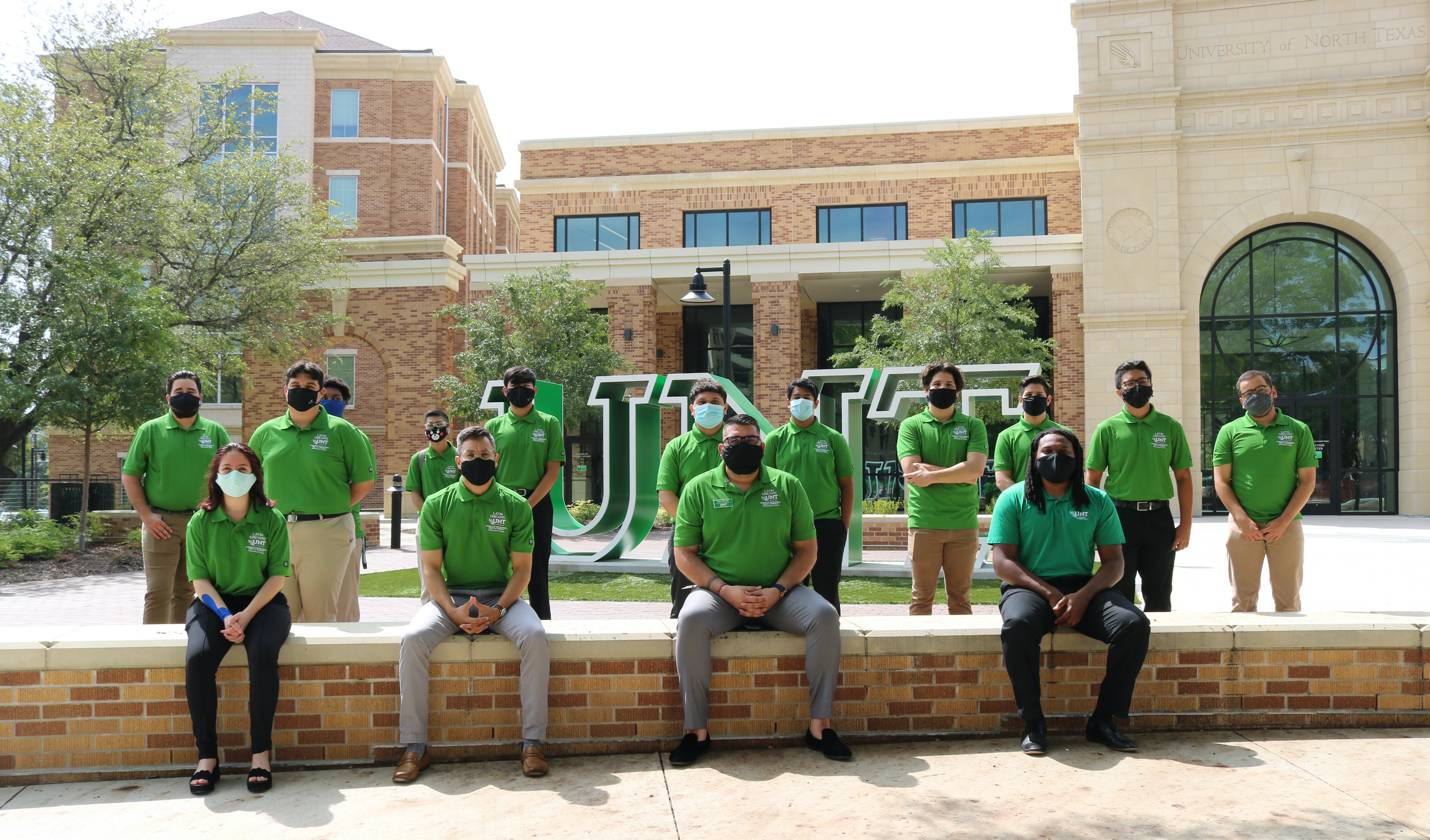 Latin Dreams mentors and students sitting in front of UNT sign